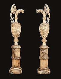 A pair of antique alabaster vases on pedestals at Butchoff Antiques.