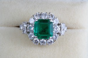 The Columbian emerald in this emerald and diamond cluster ring weighs 1.83 carats.  (14,500).