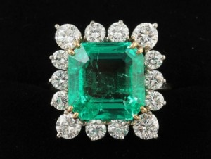 A diamond and emerald cluster ring, the trap cut emerald estimated at 9.99 ct, diamonds 2.20 carats (20,000-26,000).