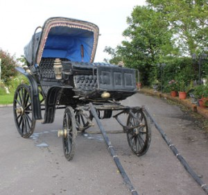 A black carriage, upholstered in leather, with original fittings