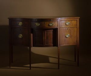 Nathan Liverant and Son LLC. A diminutive Federal Mahogany Sideboard, featuring a serpentine front, straight tapered legs and unusual floral and stringing inlay decoration. Portsmouth, New Hampshire or possibly Rhode Island, 1785 - 1810. Mahogany with Eastern White Pine secondary wood.