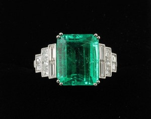 A VERY FINE QUALITY EMERALD RING, the trap cut emerald to stepped diamond shoulders. (20,000-25,000).