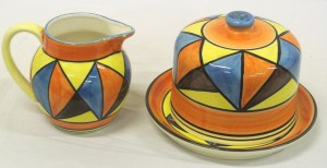 A Clarice Cliff cake dish and cover and jug, each estimated at 100-150.