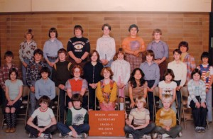 Curt Cobain: A color photograph of Kurt Cobain, later of the band Nirvana, in his fifth grade group class photo. Cobain, with his blond hair, is seen sitting on the floor holding one side of a red sign that reads, Beacon Avenue Elementary Grade - 5 Mrs. Grove  (200-300)
