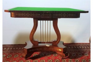 A Georgian fold over card table on platform base with lyre support (1,000-1,500).