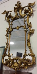 A Chippendale tradition carved wood cartouche shaped mirror with exotic bird mounts.