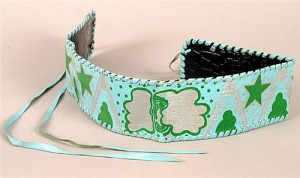 """Jimi Hendrix, painted leather strap  A pale blue leather band decorated in emerald green and silver with stars and clouds and centred with a stylised woman's face. Accompanied by a letter, dated November 7, 2013, from Bob Levin, Jimi Hendrix's U.S. manager, stating that the strap was given to Jimi Hendrix by a fan and that he wore it """"frequently around his thigh when he played"""". The letter also certifies that the item belonged to Jimi Hendrix. Also a photograph of Jimi Hendrix with Bob Levine and Steven Angel taken in New York, 8 November, 1968. 91,800-2,200)"""