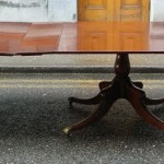 A 24 foot long mahogany dining table on four pods.