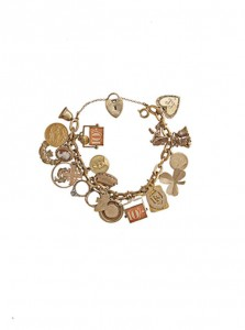 A 9 carat gold charm bracelet, the 18 carat gold fancy-link chain suspending numerous 9 carat gold charms (400-600).