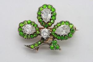 A demantoid and diamond brooch in the shape of a shamrock