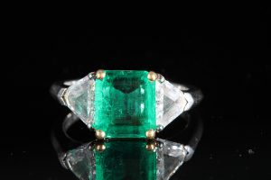 AN EMERALD AND DIAMOND THREE STONE RING (8,000-9,000)
