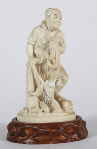 A JAPANESE IVORY CARVING, 19th Century of a fisherman with nets and fish (150-250).