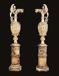 A pair of antique alabaster vases on pedestals at Butchoff Antiques.