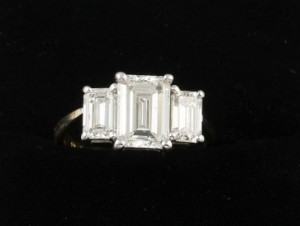 A three stone diamond ring with emerald cut diamonds, GIA certified centre stone; 2.21 ct, E colour, VVS1 clarity, estimated; weight of side stones; 0.60 ct each 22,000 - 25,000