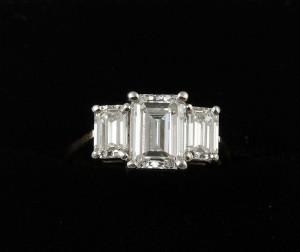 A three stone diamond ring (20,000-25,000).