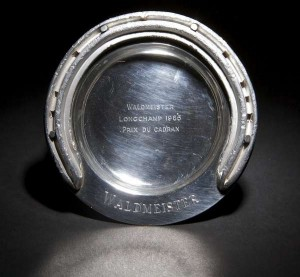 A CIRCULAR SILVER DISH WITH A MOUNTED SILVERED HORSESHOE, from the racehorse Waldmeister, Winner of Longchamps 1965 the Prix de Cadran (so inscribed), London, 1965, (100-200)