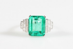 A Colombian emerald ring the trap cut emerald to stepped baguette diamond shoulders.  Emerald 6.59 carats (18,000-22,000).