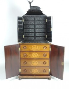 An exhibition piece of Killarney furniture surmounted by an ebonised cabinet.