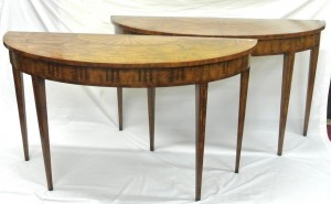 A pair of Louis XV walnut demi-lune side tables with ribbon inlay