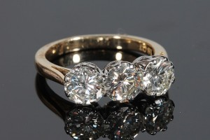 A THREE STONE DIAMOND RING (8,500-9,000)