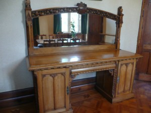 An oak pedestal sideboard with the Collis-Sandes crest.