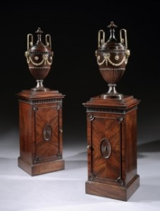 A PAIR OF GEORGE III BRASS MOUNTED DINING ROOM URNS ON PEDESTALS PROBABLY BY THOMAS CHIPPENDALE AT RONALD PHILLIPS