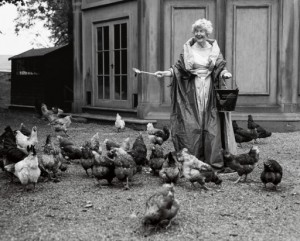 Deborah, Duchess of Devonshire feeding her chickens at Chatsworth, 1995 wearing a Balmain ball gown and pearls. Copyright Bruce Weber