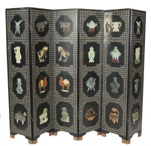 A LARGE CHINESE SIX FOLD INLAID EBON SCREEN each panel decorated with mother of pearl diamond field and set with four carved jadeite reliefs depicting houses, urns, cows, camels etc. (1,000-1,500)