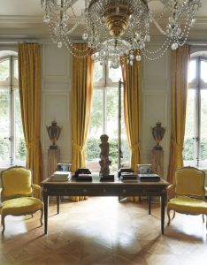 The living room, decorated in light grey panelling conceived by Emilio Terry,