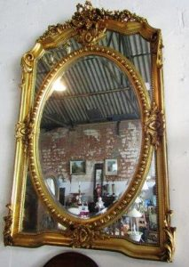 An oval carved gilt wood mirror (200-300)