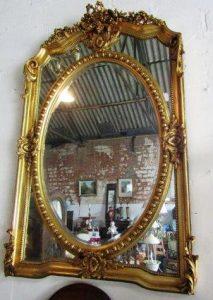 An oval carved gilt wood mirror (200-300)